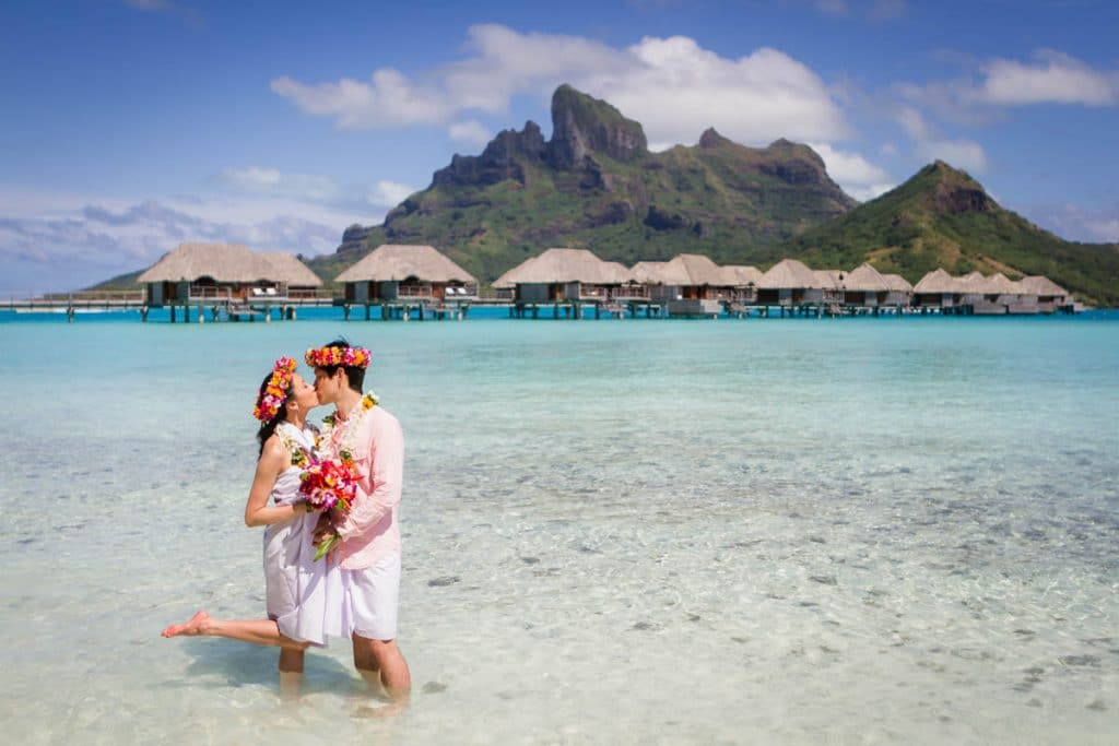 bride kissing in front of mount Otemanu in traditional pareo