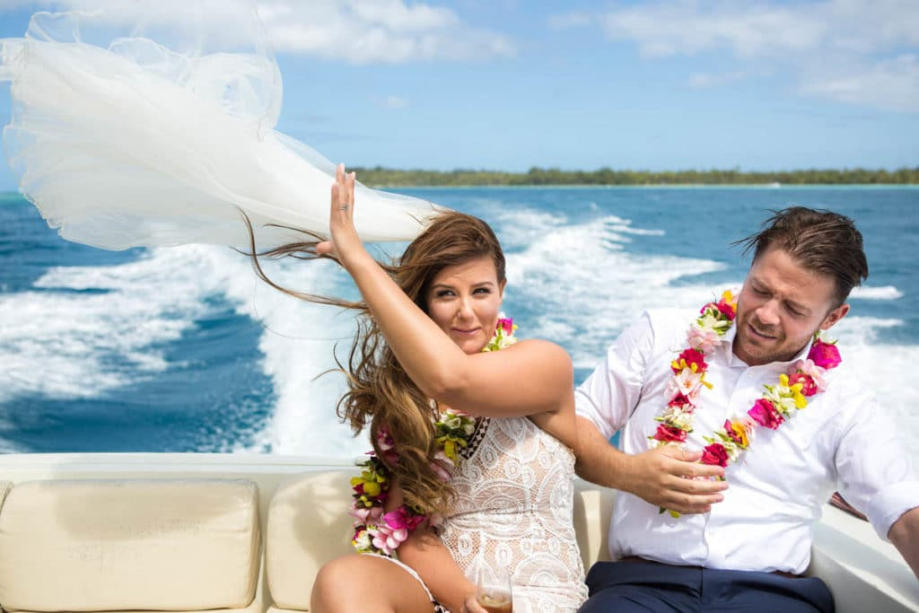 bride on a boat ride back, veil flying in the wind