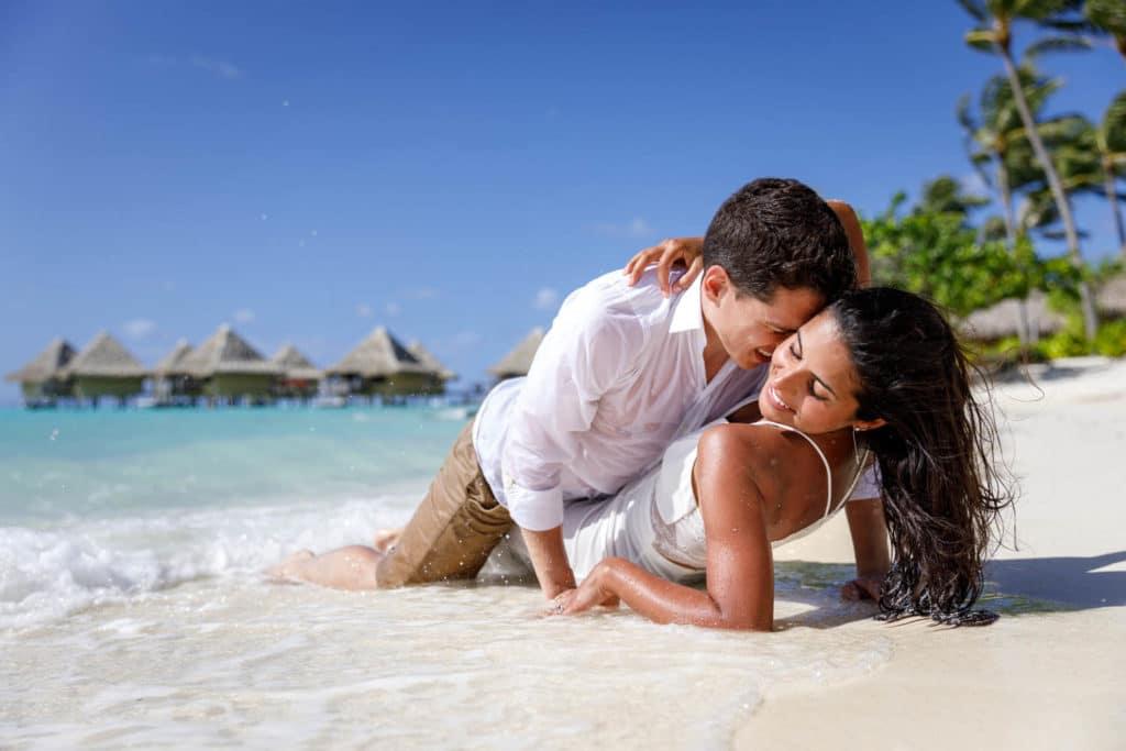 Livia & Marc lying on the beach kiss in bora bora