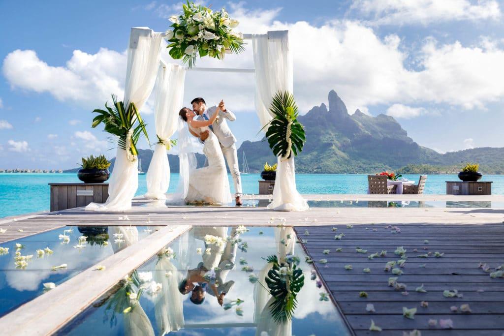 couple kissing under the arch of the lagoon restaurant at st regis resort bora bora