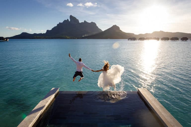 bride and groom trashing the dress jumping from the pool of four seasons resort bora bora