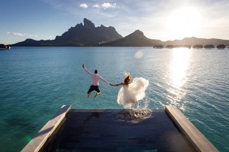 bride and groom trashing the dress jumping from the pool of four seasons resort bora bora