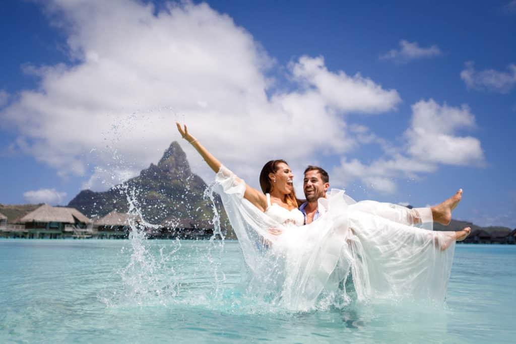 Couple splashing water and trashing the dress