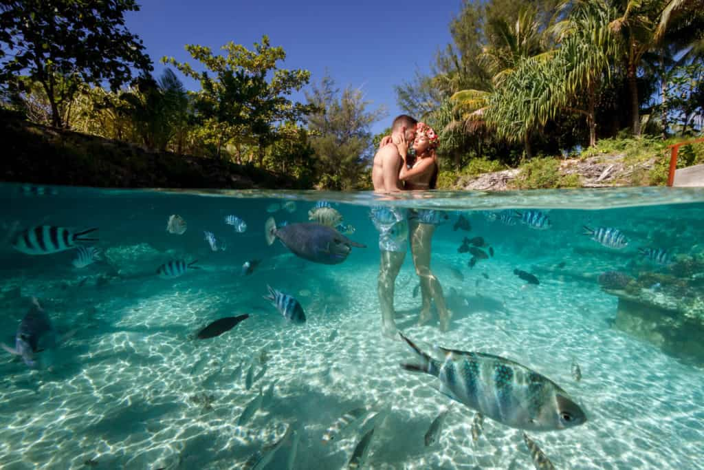 over-under picture of a couple inside the lagoon of the four seasons resort Bora Bora