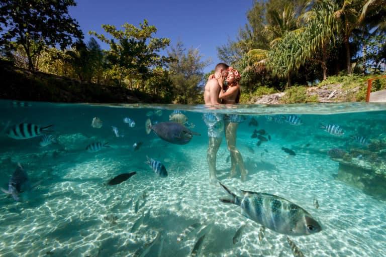 couple inside the water of four seasons Bora Bora lagoon