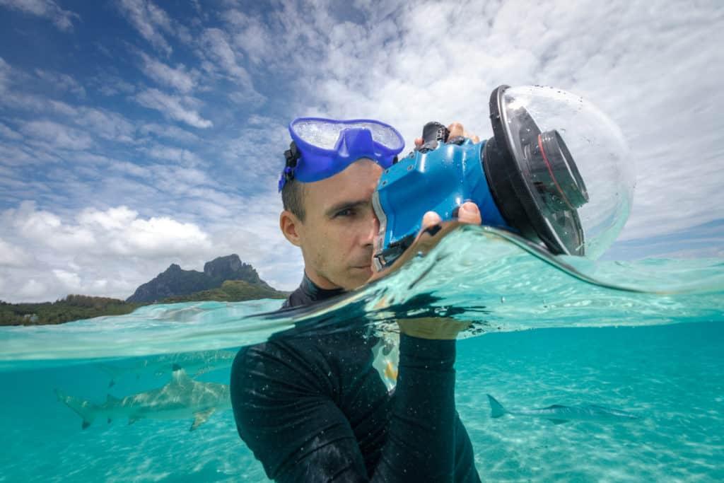 Bora Bora photographer Damien Gobron holding his underwater equipment